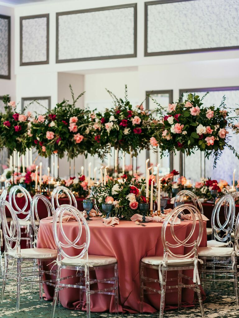 Lush green, pink and white floral centerpieces at wedding reception with coral tablecloth