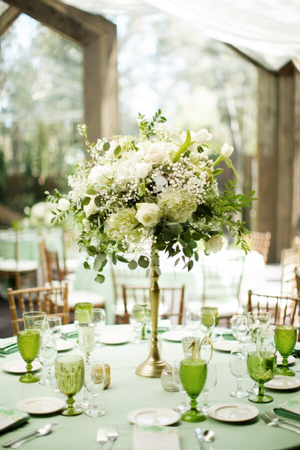 In addition to raised gold-stemmed flower arrangements made with white roses, peonies and eucalyptus, each table was set with vintage green glassware and brassy candleholders.