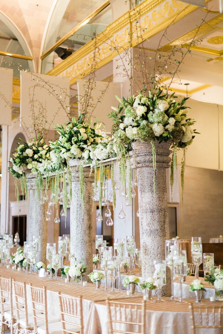 "Abbi and Cameron wanted dramatic tall centerpieces to anchor the space in Terminal Station. ""I've seen a large estate table with tall center pieces done in this room many times so we wanted to do something different, something never done here before!"" says Abbi. ""We planned for tall columns supporting large arrangements in the center of the table to create a focal point in the center of the room."""