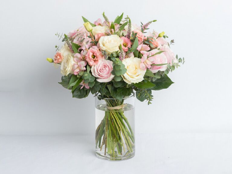 Bouquet of white and pink flowers with greenery in glass vase