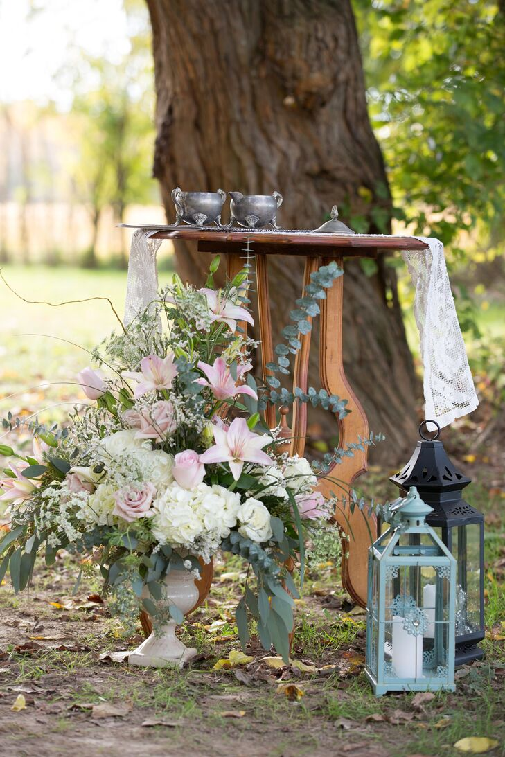 Stephanie and Patrick decorated the outdoor ceremony with vintage decor. The altar area had arrangements of blush and white flowers, lanterns and tea services with lace doilies.