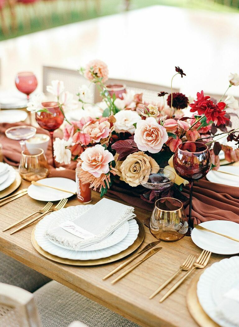 Vibrant pink-and-burgundy floral centerpiece on farm table
