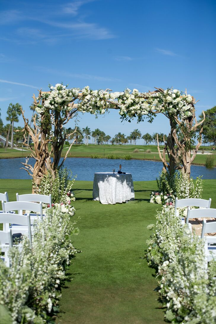 """Taking advantage of the sunshine and waterfront setting, Emily and Jason hosted their ceremony outdoors overlooking swaying palm trees and a quaint pond. """"Our florist lined the aisle with flowers that looked like they were growing from the grass—this was so pretty and gave the ceremony location a whimsical, garden vibe,"""" Emily says. The wedding arch was the ceremony's showstopper, with fluffy hydrangeas and textured greenery adorning a beachy driftwood structure."""