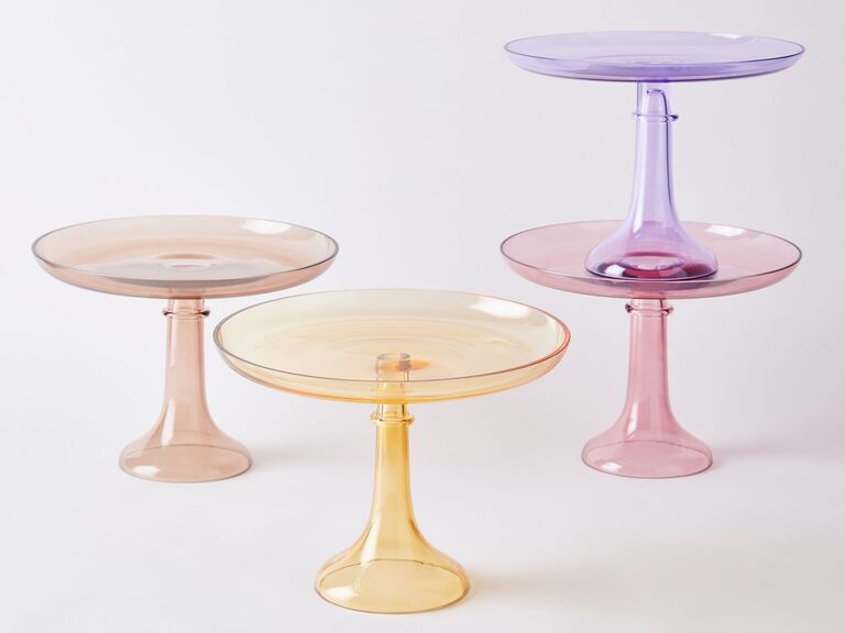 Four glass wedding cake pedestals in different pastel shades