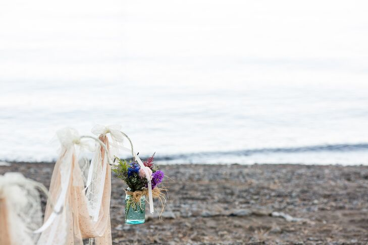 The ceremony took place on the sand by the lakefront, which needed little decor thanks to the beautiful natural surroundings. The aisle was lined with white iron hooks that had lace and ribbon draped over them, with wildflowers arranged inside hanging mason jars.