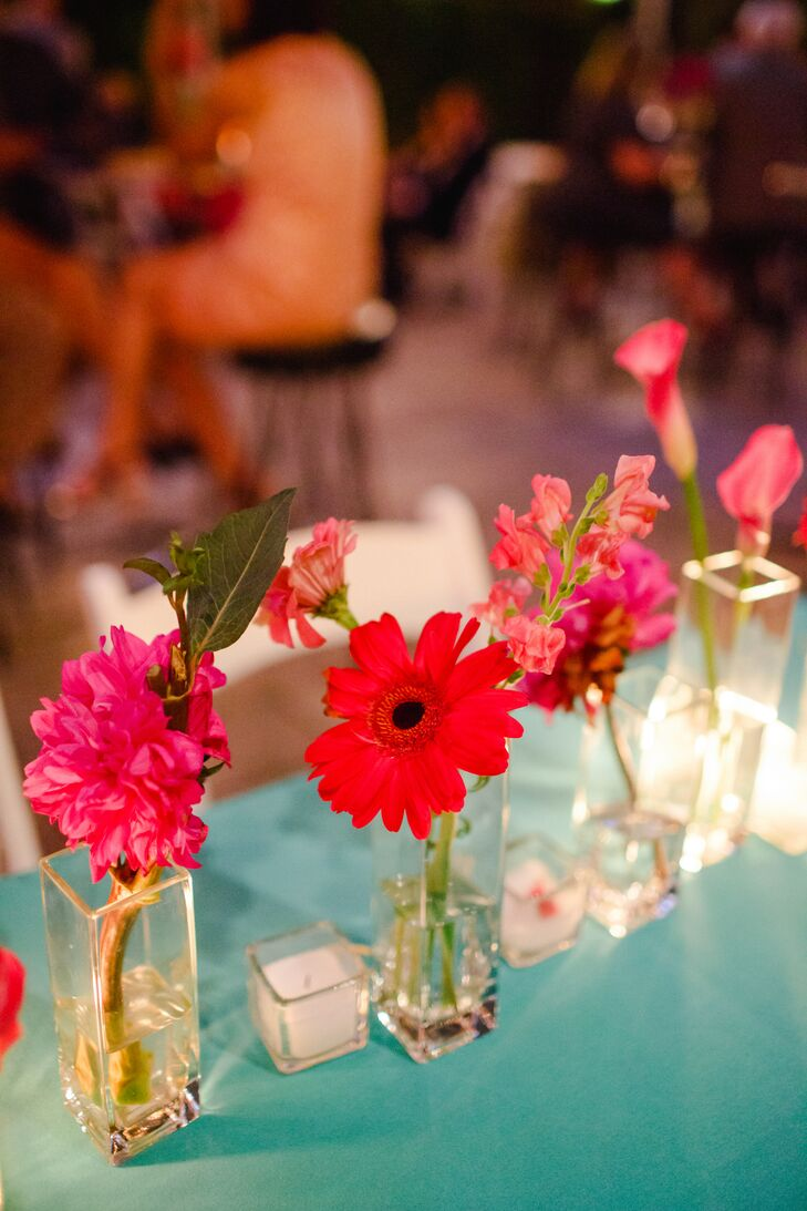 """When it came to the reception decor, Risa and Michael kept things simple yet colorful, opting out of traditional centerpieces for playful bud vases filled with bright red and pink flowers and dressing the tables with bright turquoise linens. The decision allowed both the architectural features at the Foundry in Long Island City, New York, and the couple's personalities to shine through. """"We did not have any major centerpieces, formal seating, place settings or name cards,"""" Risa  says. """"We just wanted to marry each other and have a huge dance party. And make music, dancing and color the focus of the whole thing."""""""