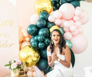 Bride sitting in front of teal-and-pink balloon installation