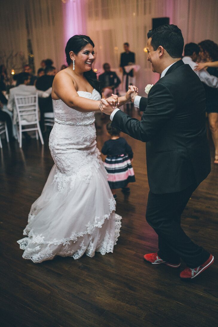 The couple, who met while salsa dancing, performed a bachata number for their first dance. The bride wore salsa shoes and the groom changed into comfortable red sneakers for their reception at Belle Mer in Newport, Rhode Island.
