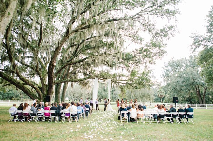 Wanting to highlight their venue, Shelby and Zack kept to almost all-white decor. Their guests sat in rows of white folding chairs accented by tons of classic, ivory skeleton magnolia leaves scattered over the aisle. Their wedding arch was even made with ivory fabric draped across a nearby oak tree.