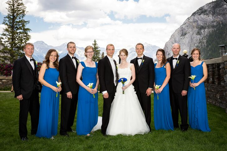 The bridesmaids wore bright blue floor length gowns, while the groomsmen wore formal black tuxedos.