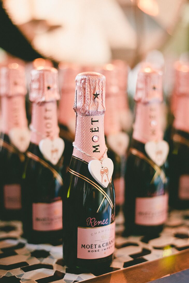 """Patricia and Christopher ditched tradition and had fun with their escort cards, decorating mini Moet Rose champagne bottles with wooden hearts bearing a tennis racket motif. The bottles were displayed alongside a rose gold sign that read, """"Time top pop champagne and drop it to the beat, but first find your seat."""""""