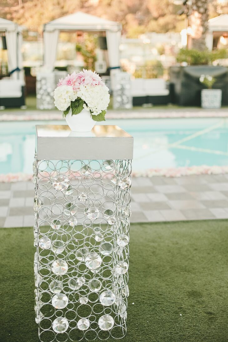 Cocktail hour took place around the pool on The London's rooftop. Small ultra modern cocktail tables dotted the lawn, the twinkling crystal embellishments and metallic tops glittering in the late afternoon sunlight. To create a cohesive look from ceremony straight through to the reception, the couple topped the tables with soft ivory and pink hydrangeas and dahlias.