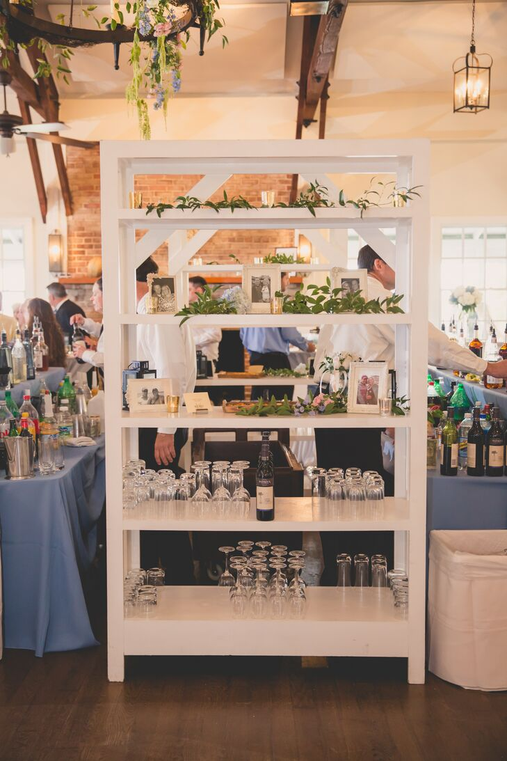 By the bar at the reception, a white bookcase featured photos of Jenna and Joshua and greenery on its shelves.