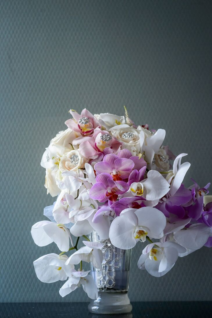 Since orchids are Nkenna's favorite flower, the striking blooms made an appearance in her bouquet. The arrangement was filled with cascades of white and vibrant purple orchids, offset by cream roses and bit of bling to play up the evening's ultra-glam vibe.