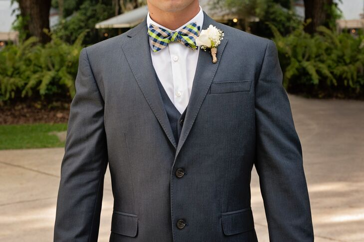Jaime added a whimsical touch to his wedding day look. He wore a navy blue suit from JC Penney with a festive green, tan and navy bow tie as well as a white rose boutonniere. For an unexpected touch, he also wore navy Converse shoes.