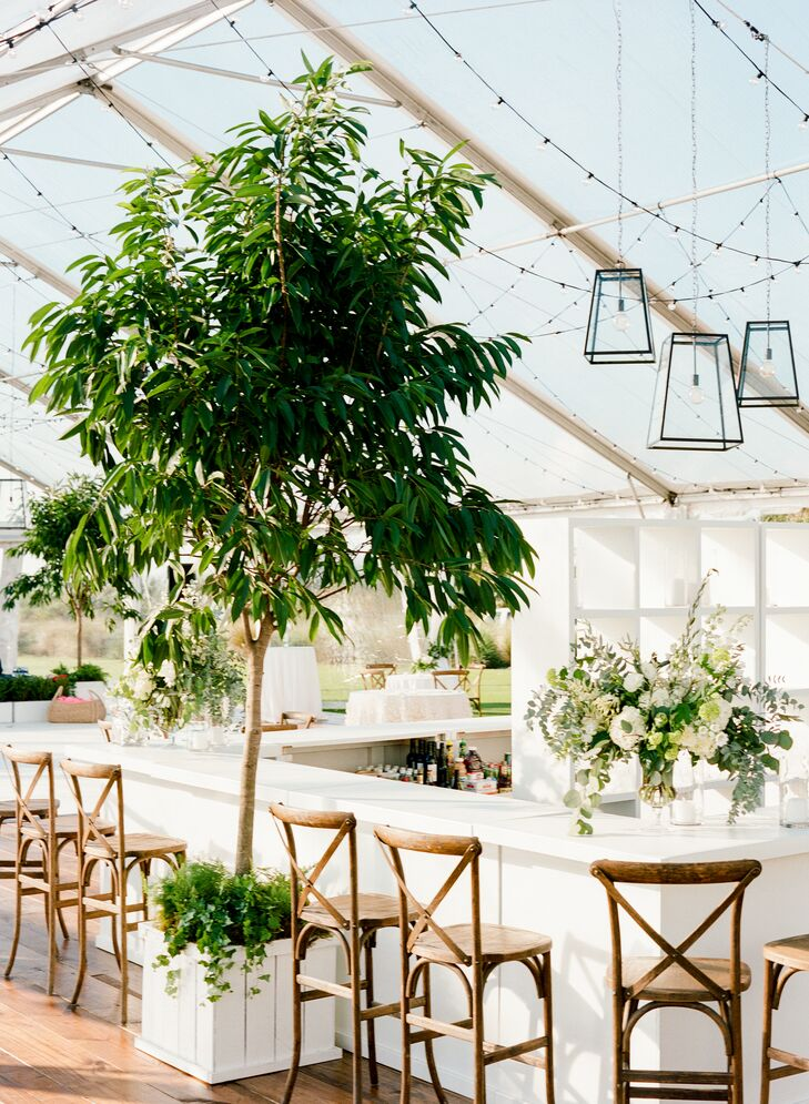Caroline and Gil's four-sided bar was strategically placed in the middle of their clear-top tent. The watering hole was gussied up with potted trees, lush floral arrangements, string lights, lanterns and wooden cross-back barstools.