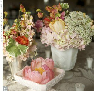 Milk-glass vases, which the bride found on eBay, held ranunculus, Queen Anne's lace, tulips, peonies, stock and hydrangeas. Underneath, damask linens added an antique vibe.