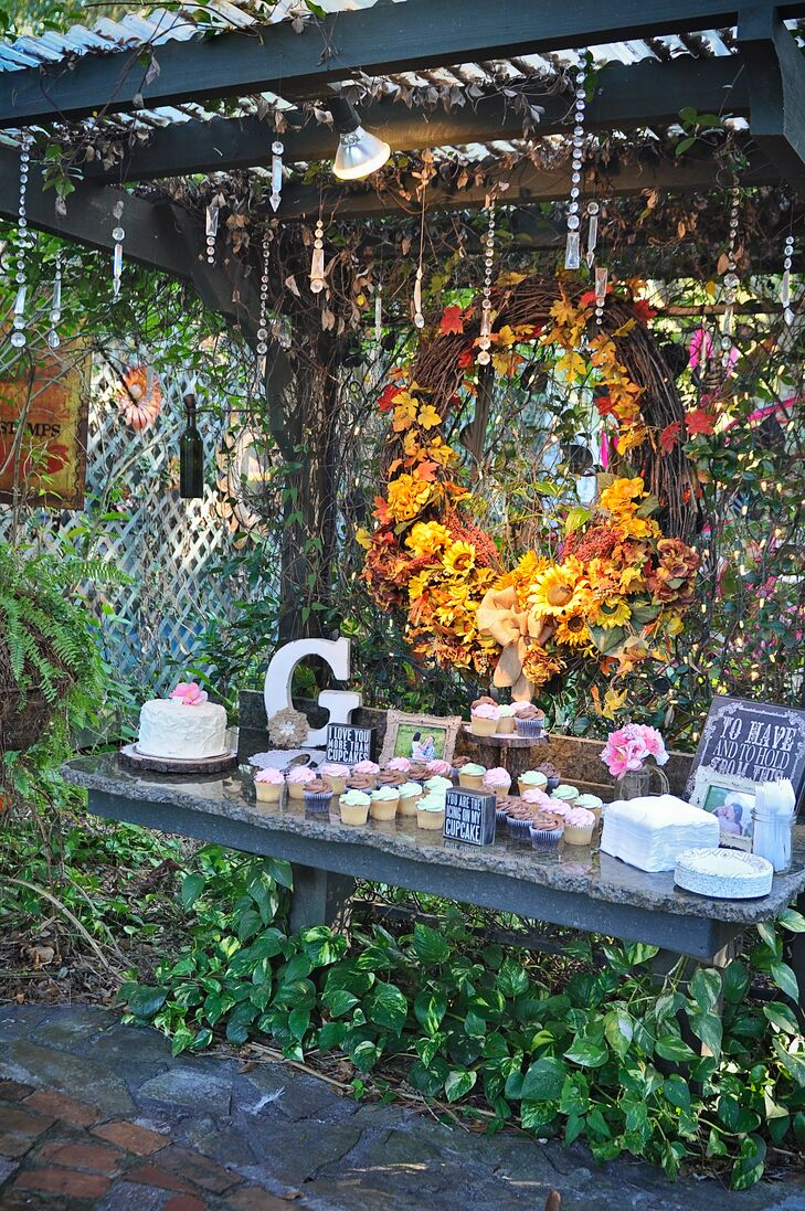 After a dinner filled with barbecue favorites, their 45 guests had the option of a few sweets. Three types of cupcakes as well as a single-tier buttercream cake from a local Publix were all available for them to savor. The decor made it even more enticing with ivy popping out from beneath the stand and a grandiose wreath filled with fabric sunflowers and fall leaves as the backdrop.
