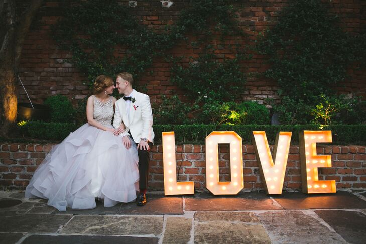 Vintage-inspired LOVE marquee lights add a whimsical touch to the couple's courtyard reception.