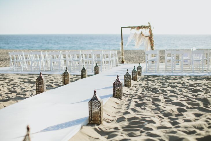 "A sturdy white platform aisle lined with lanterns led to the dream catcher wedding arch where Gwynne and David exchanged vows. ""I wanted a boho beach wedding with rich orange sunset colors in the flowers,"" Gwynne says. ""The Sunset Restaurant was the perfect location because we were able to have our ceremony right on the beach at sunset."""