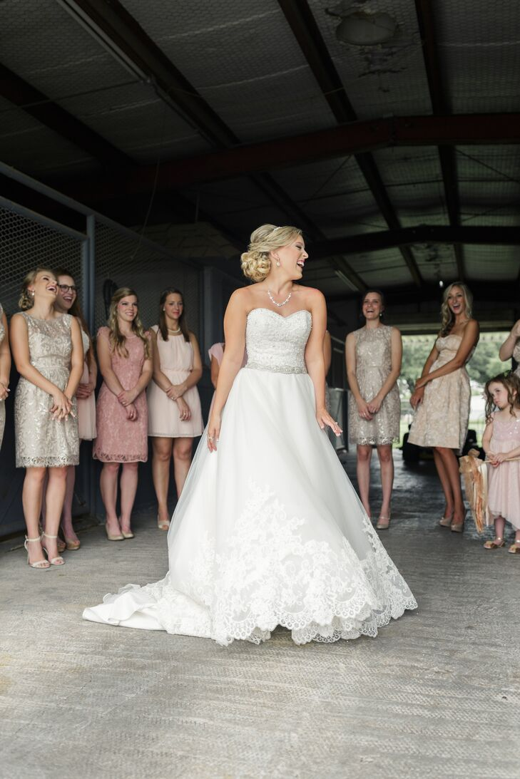 When it was time for Blair to put on her wedding dress, instead of the on-site cottage, she decided to sneak down to the rustic horse barn to get ready. Using her bridesmaids as cover, she donned an A-line gown with a fitted sweetheart neckline beaded bodice, embellished belt and lace scalloping on the ends of the skirt.