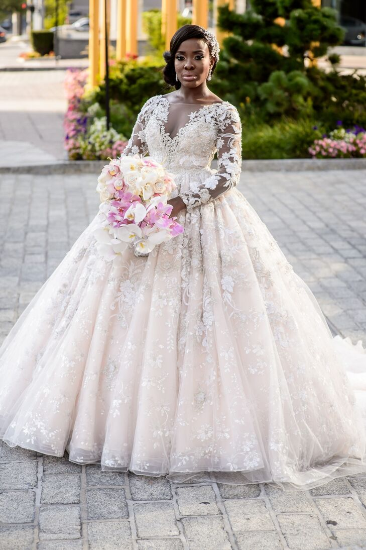 """Nkenna originally had her heart set on a form-fitting mermaid-style gown with a dramatic skirt, but after trying on countless dresses, nothing delivered the wow factor she was after. She decided to give other styles a shot and headed to Bridal Reflections to try on a YSA Makino ball gown her sister thought would be perfect for the glamorous fete. """"Once I got into the dress, that was it—I had found my dress,"""" Nkenna says. With its full skirt, embroidered floral overlay and long illusion sleeves, the ball gown was a bona fide showstopper. """"I wanted wow factor, and this was it. Nobody expected me in a ball gown,"""" she says. """"The mermaid-style fit for me looked too predictable. Looking back, it was the best decision ever!"""""""