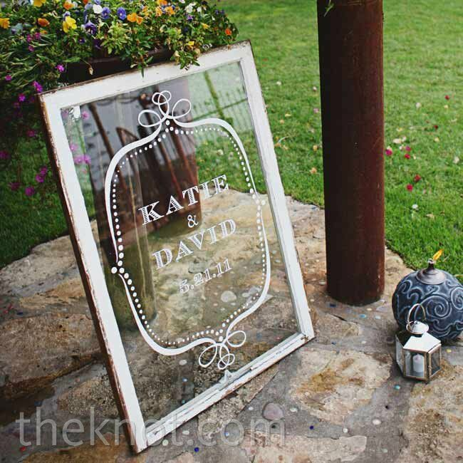 A vintage window painted with the couple's name and wedding date decorated the path to the ceremony.