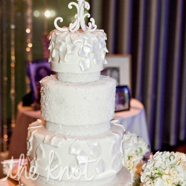 An elegant topper and ivory sugar rose petals adorned the four-tiered fondant cake.