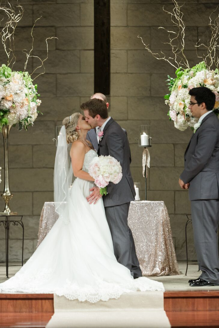 """Blair attended Woodcreek Church her whole life, so naturally she wanted to marry Alex here! They said """"I do"""" between two tall arrangements of hydrangeas, garden roses and curly willow. A special touch you can't see: Both Blair and Alex have their favorite bible verse written in blue inside their shoes."""