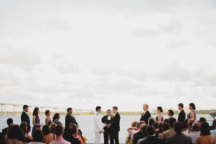 "Each groom was escorted down the aisle by his mom and Michael's dad officiated the waterfront nuptials. ""We really loved the wording of our original wedding at San Francisco City Hall,"" says Joey. ""We got a copy of the language and gave it to Michael's dad to read during our ceremony."""