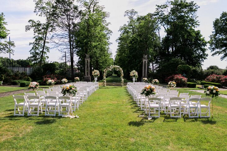 The ceremony took place on the Guggenheim Mansion's great lawn, overlooking rows of lush trees at the Village Club of Sands Point in Sands Point, New York. Noel and Tim exchanged heartfelt vows under a wrought iron wedding arch decorated with wispy vines, greenery and full peach, cream and coral garden roses, hydrangeas and more. Large stone urns lined the aisles, bursting with berries, stock, amaranths, hydrangeas and roses.
