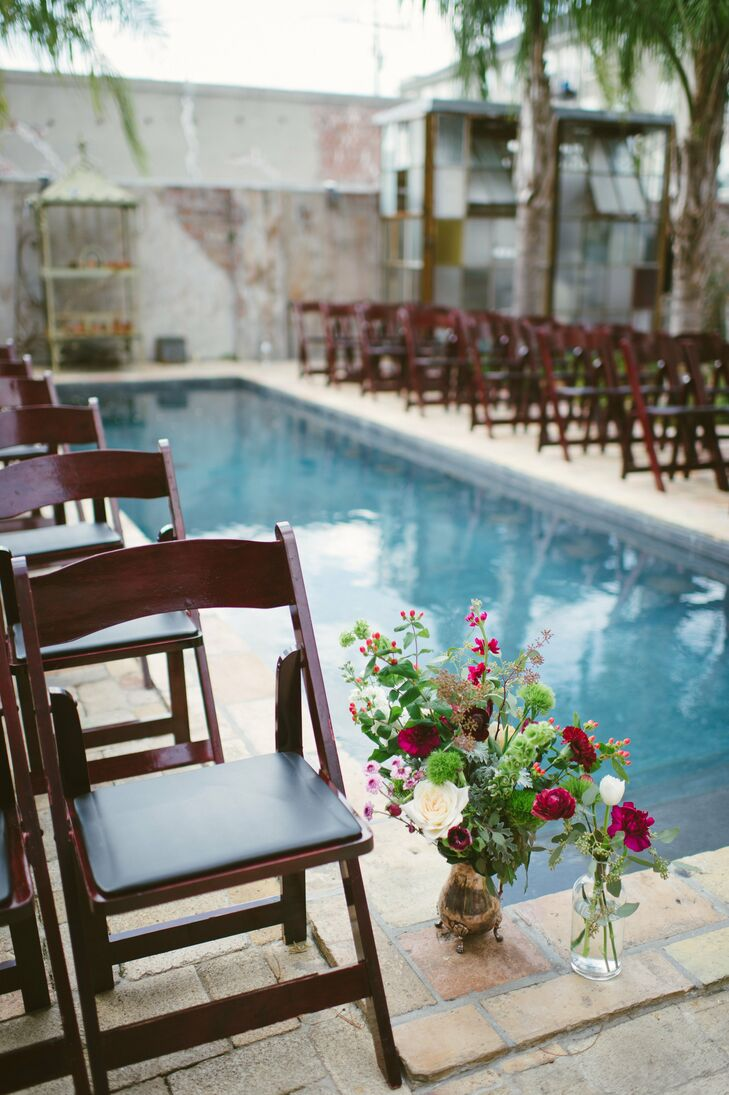The ceremony was held in the venue's brick-faced courtyard. Seating was arranged around the long reflecting pool with textured floral arrangements with deep shades of red and purple placed at the ceremony altar.