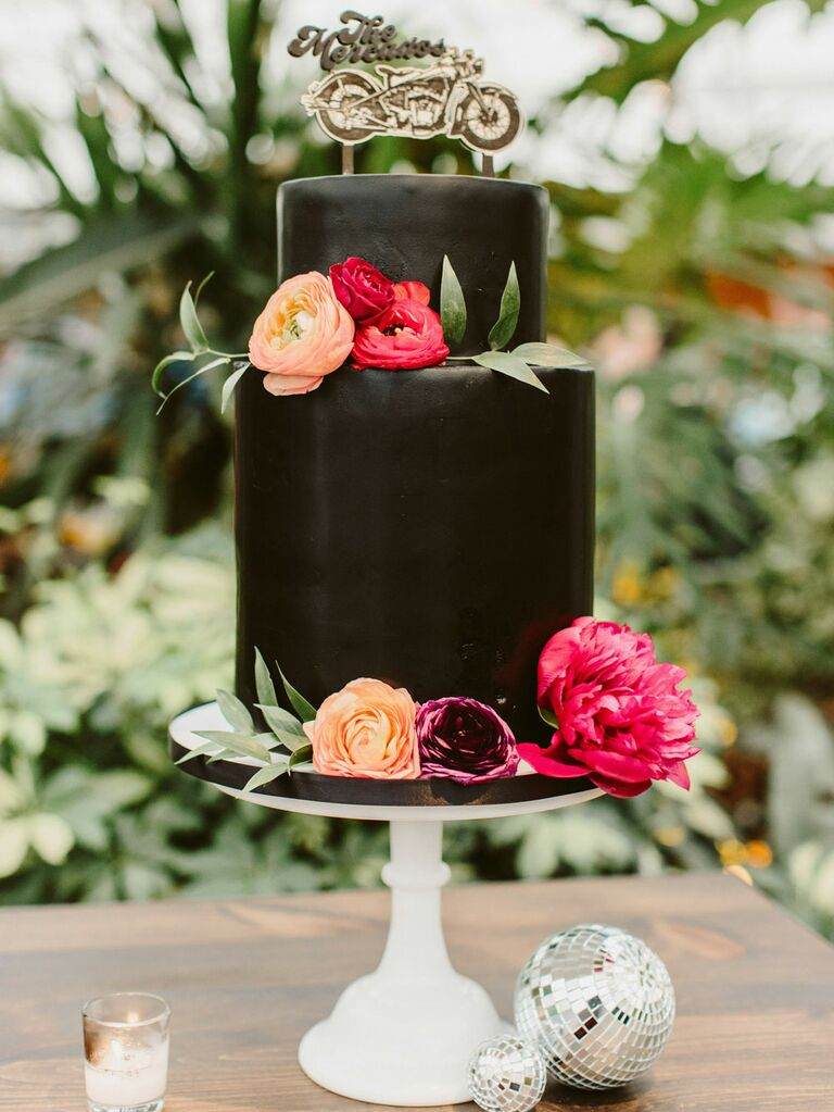 Small two-tier black wedding cake with pink and orange flowers and custom motorcycle cake topper