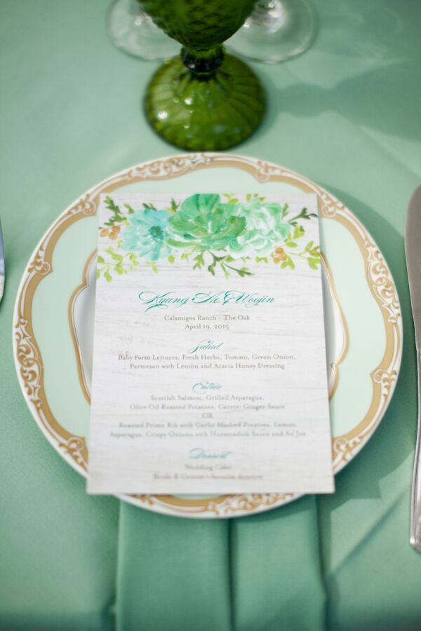 The garden wedding's vintage-inspired table settings included pale-green tablecloths, gold and green plates and textured green glassware.