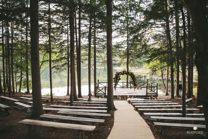 """Amy and Geoff's ceremony was held outdoors, cloistered in the woods with a lake as the backdrop at Cedar Lakes Estate in Port Jervis, New York. """"Since I'm used to shooting TV, I timed the ceremony with the sunset so that the lake would be gleaming as we stood before everyone,"""" Amy says. The ceremony site was simply decorated with an arch of greenery and flowers."""