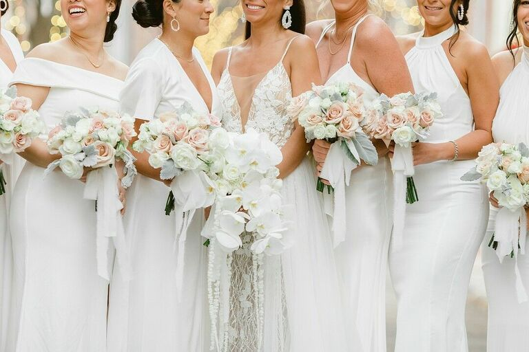 Bridal party in white dresses with white floral bouquets