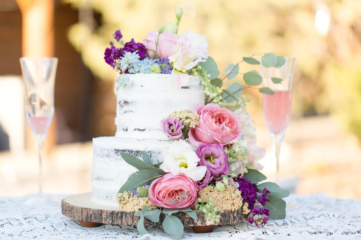 Abigail asked a friend to make her roughly frosted wedding cake, topped with pink and violet blossoms and eucalyptus.