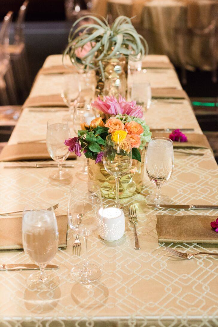 The reception had an eclectic mix of long, round and square tables and lounge areas. Centerpieces in assorted gold vessels and white ceramic vases topped gold table linens.