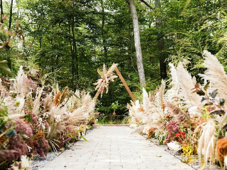 Lush pampas grass arrangements along outdoor wedding ceremony aisle and at altar