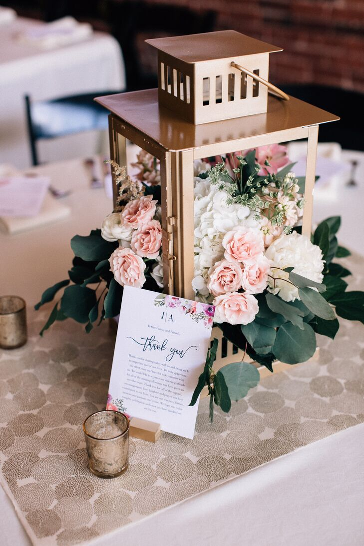 A lantern doubled as a centerpiece filled with pink and ivory roses.