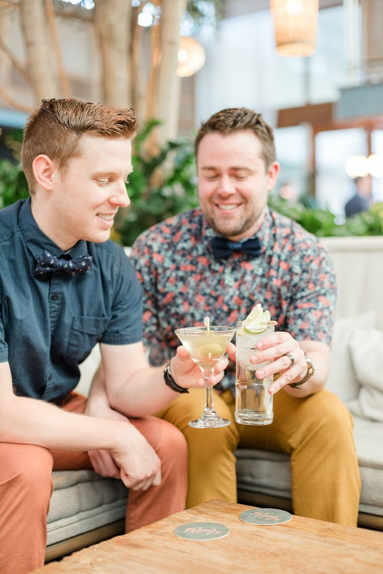 Grooms toast with craft cocktails during engagement photo shoot