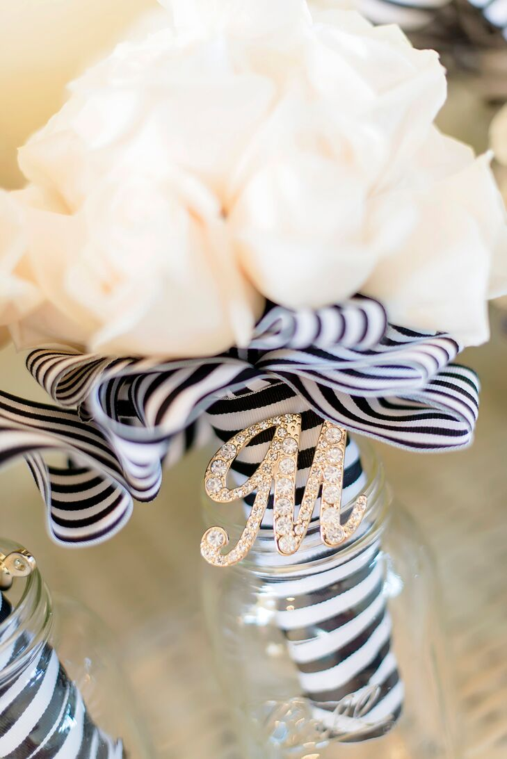 The bridesmaids carried a bouquet of white roses wrapped in a black-and-white-striped ribbon. The bride incorporated large blush roses and white peonies into her bouquet as well.