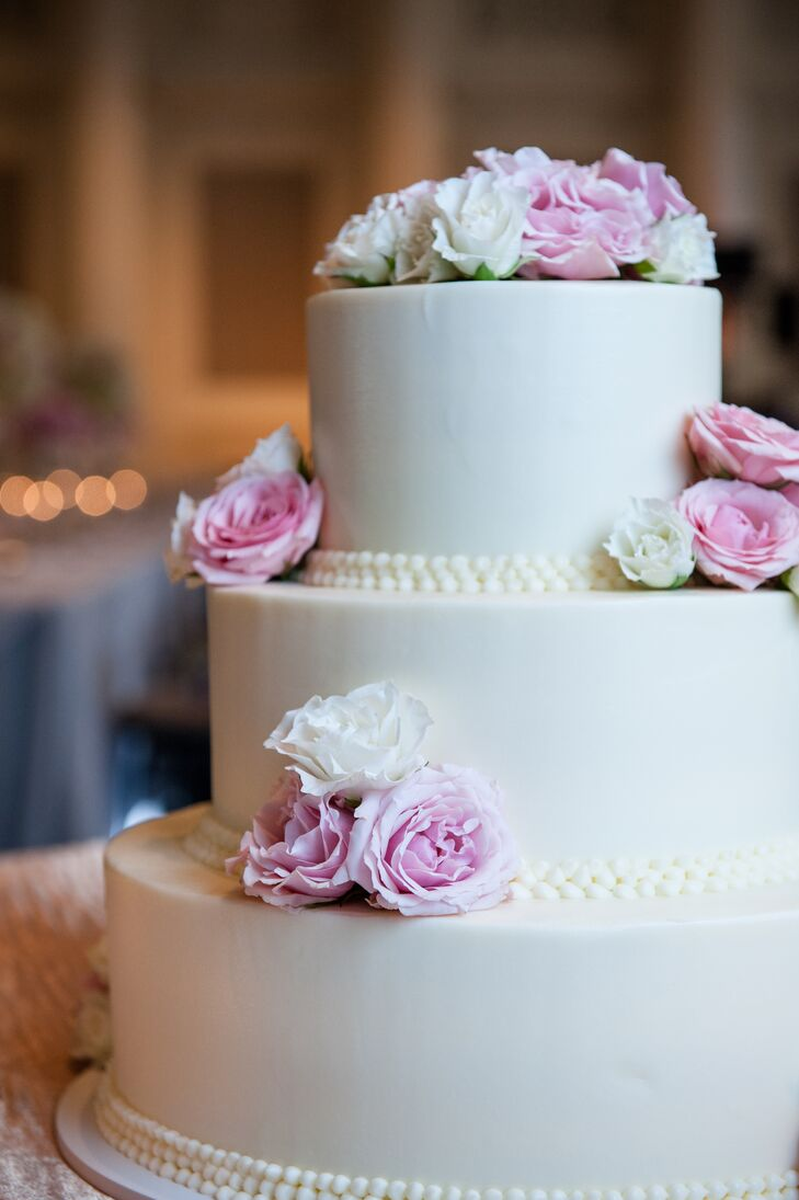 The couple's three-tiered wedding cake was classic white, topped with pink and white roses that matched the color palette of the rest of the wedding decor.