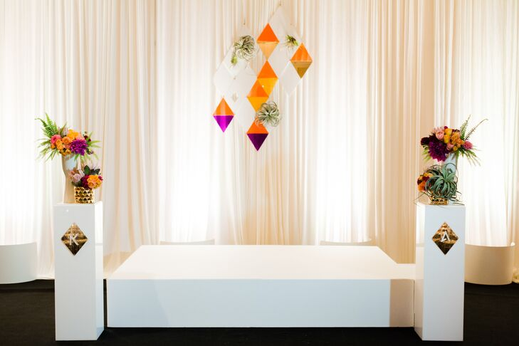 Kelly and Adam brought in white draping and black carpeting, transforming the ballroom space for the ceremony. Custom laser cut shapes provided a colorful and unique backdrop for their I do's.