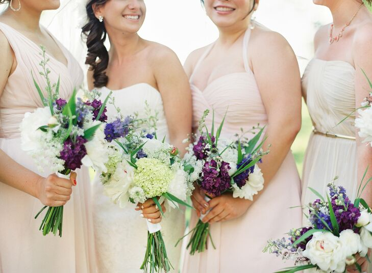 The bridesmaid arrangements were smaller than the bride's bouquet and popped with deep purple lilacs.