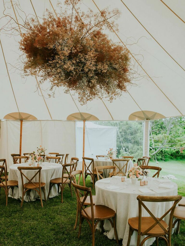 Neutral statement floral chandelier hanging from wedding tent