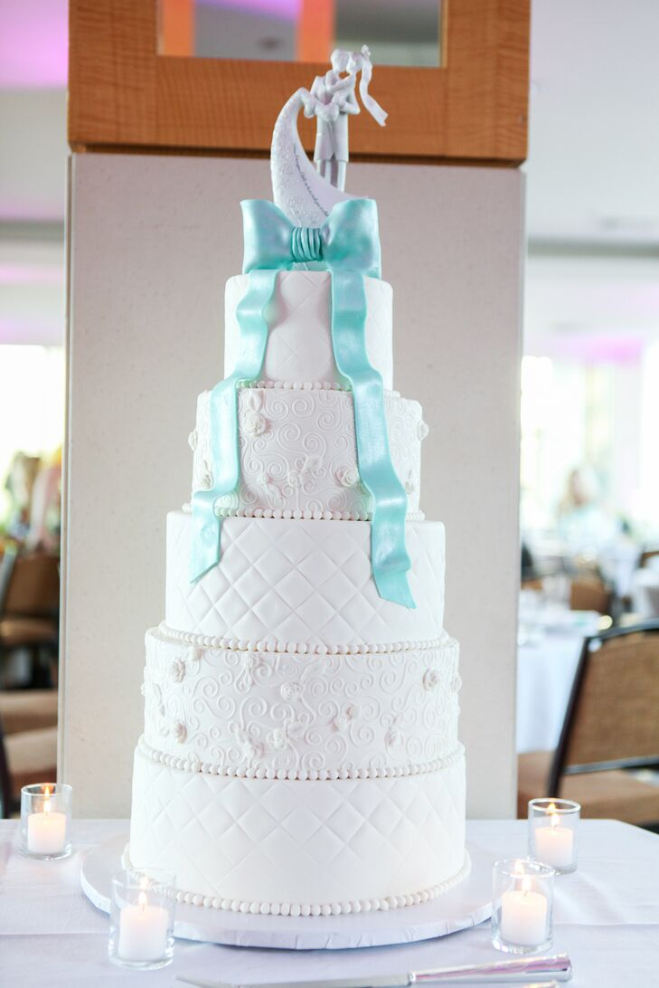 A Tiffany blue fondant bow with cascading ribbons added a graceful pop of color to this tall, elegant five-tier wedding cake. The modern white tiers alternated between quilted textures and detailed spirals with delicate flowers.
