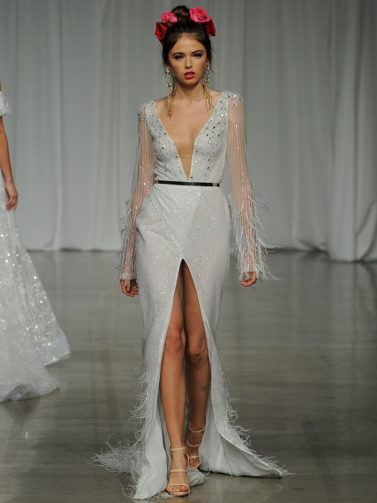 Julie Vino Spring 2019 glamorous wedding dress with a plunging illusion neckline, sheer feathered long sleeves and a high front slit