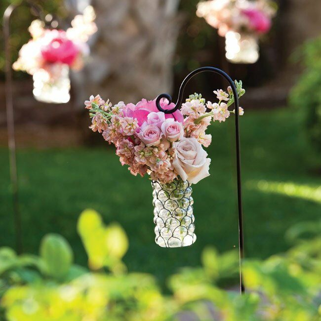 The path to the ceremony site was lined with vases of pink flowers hanging from shepherd's hooks.