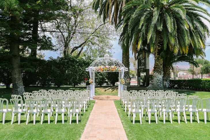 The ceremony took place outside at Glen Tavern Inn in Santa Paula, California, where white chairs were organized into rows that faced the white iron wedding arch. The arch had accents of bright yellow sunflowers and coral dahlias on top, which gave the white decor a pop of color!rn